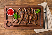 Roasted lamb ribs with sause on wooden background, top view