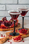 Pomegranate cocktail and ripe red pomegranate fruit on white wooden table