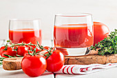 Tomato Juice and Fresh Tomatoes on a White Wooden Background