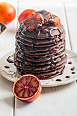 Chocolate pancakes with orange and chocolate sauce for breakfast on a white wooden background