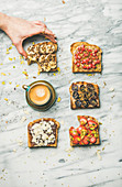 Vegan wholegrain toasts with fruit, seeds, nuts, peanut butter, cup of espresso and woman hand over marble background