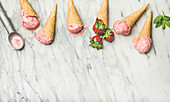 Yogurt ice cream with strawberries in waffle cones over grey marble background