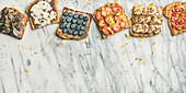 Vegane Vollkorntoasts süss belegt mit Obst, Samen, Nüssen und Erdnussbutter