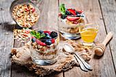 Selbstgemachter Joghurt mit Granola und Beeren in Gläsern
