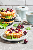 Small tarts with cream cheese and fresh cherries on gray background