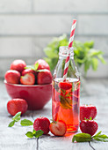 Sommerliches Erfrischungsgetränk mit Erdbeeren in Glasflasche