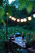 A string of lanterns above a rustic garden table with drinks and snacks