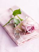 Romantisches Gedeck mit Rose, Gabel und Stoffserviette