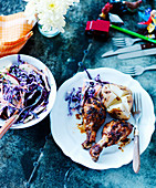 Grilled chicken drumsticks with a baked potato and red cabbage salad