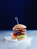 A burger with bacon, tomatoes and salad