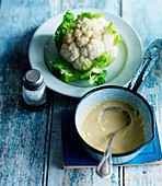 A cauliflower with cheese sauce in a pan