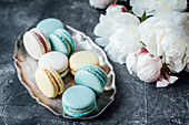 Macaroons on a silver dish next to peonies