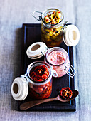 Tomatoes, hummus and preserved olives in flip-top jars