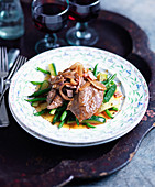 Lamb's liver with bacon and onions on a bed of green vegetables