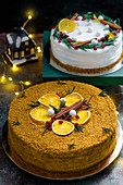 Two different Christmas cakes with oranges and cinnamon sticks