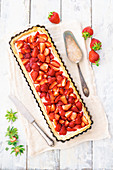 Strawberry tart with a cream cheese and vanilla cream in a rectangular tart tin