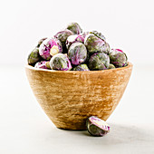 Purple Brussels sprouts in a wooden bowl on concrete background