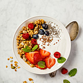 Bowl of homemade granola with yogurt and fresh berries on white marble background