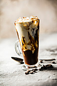 Iced coffee in a tall glass with cream poured over on a rustic table