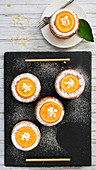 Small round orange cakes decorated with glazed orange slices, flaked almonds and powdered sugar and served on a black slate tray