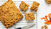 Apricot, pumpkin seed and oatmeal slice cut into pieces, cooling on a wire rack with of dried apricots and walnuts