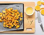 Small pieces on butternut on a baking tray with a bowl of oil and a knife
