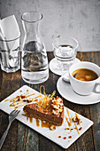 Ein Stück Karamelltorte mit glasierten Nüssen serviert mit Wasser und Kaffee