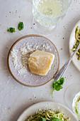 Parmesan: Käsestück und gerieben auf Teller (Aufsicht)