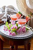 Zwei Gläser Erdbeer-Rhabarber-Cocktail dekoriert mit Kirschblüten