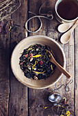 Herbal dry tea leaves with wild flowers and dried fruit on wooden rustic table