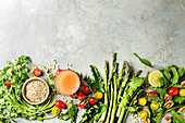 Variety of vegetarian healthy eating food ingredients. Green asparagus, herbs, tomatoes, nuts, wheat corns, dandelion leaves, glass of juice