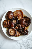 Soaked siitake mushrooms in white bowl on white marble table