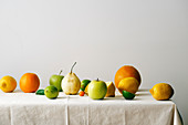 Citrus fruits, pear and apples on a table covered with linen tablecloth
