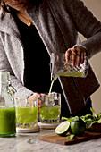 Frau schenkt Gurken-Limetten-Cocktail ein