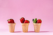 Fresh strawberries in waffle cups over pink pastel pin-up background