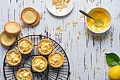 Lemon tartlets decorated with toasted almond flakes, unfilled pastry cases and a bowl of lemon butter