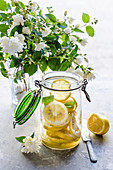 Making preserved lemon, sliced fresh lemons in a jar