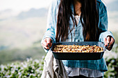 Woman holding baked granola cereal on a farm