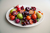 Obstteller mit Mini-Kiwis, Granatapfel, Trauben, Birnen, Pflaumen und Nektarinen