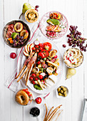 Variety of snacks prepared for picnic wine summer party with fresh fruits, vegetables, prosciutto and chesse