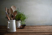 Rustic still life of a kitchen counter with worn wooden utensils in a porcelain pitcher and a lovely tangled oregano plant in the background