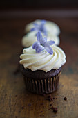 Mini chocolate cupcakes with cream topping and purple flowers