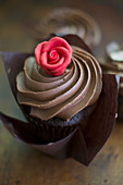 A chocolate cupcake with a cream topping and a marzipan rose