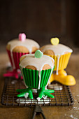 Lemon muffins with icing in colourful plastic cases with legs
