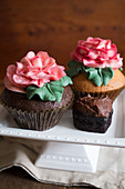 Cupcakes decorated with large sugar roses on a cake stand