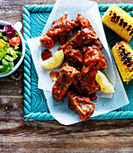 Spareribs with corn on the cob, lemons and salad