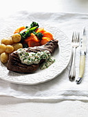 A beef steak with potatoes, carrots, broccoli and parsley sauce