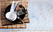 A wok, small bowls, serving spoons, glasses and chopsticks on a bamboo mat