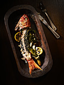 Red Snapper fish with bones on a wood plate