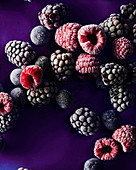 Still life of raspberries, blackberries and blueberries that show frost